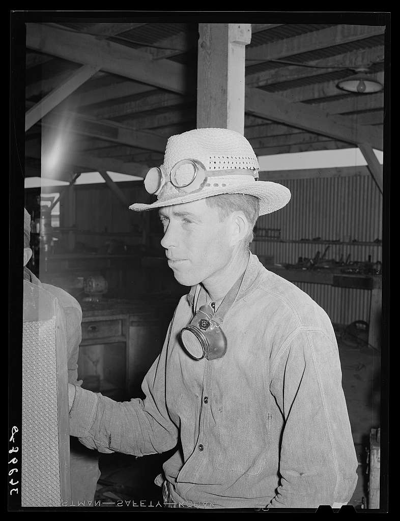 Men who work on the hay chopping machine wear goggles and masks. Casa Grande Valley Farms, Pinal County, Arizona