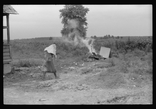 Migrant disposing of trash before leaving Belcross, North Carolina for another job at Onley, Virginia