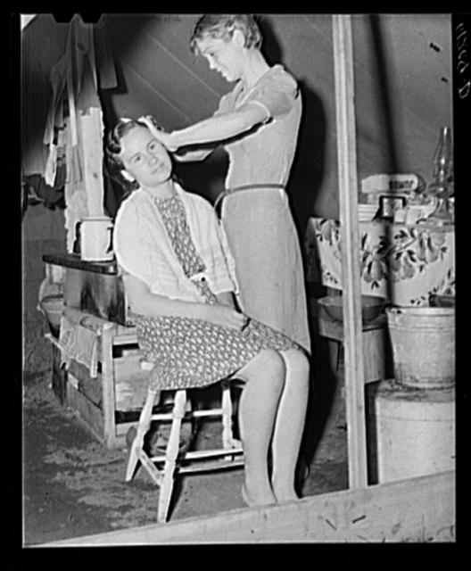 Migrant girl fixing her sister's hair. Roadside camp of fruit worker. Berrien County, Michigan