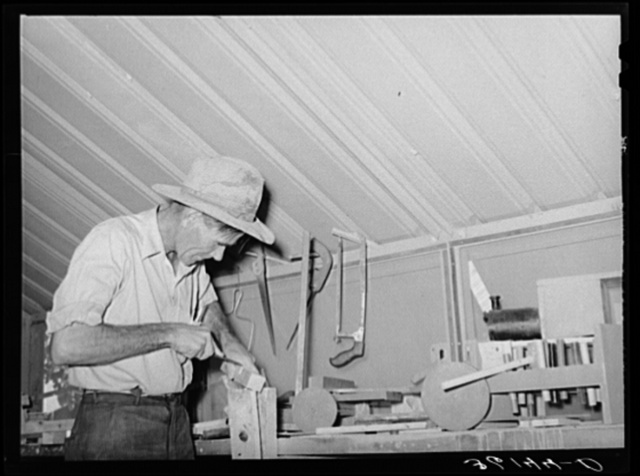 Migratory agricultural laborer making toys for the WPA (Work Projects Administration) nursery school at the Agua Fria migratory labor camp, Arizona. Farm work was slack and this man volunteered to make and repair nursery supplies during his idle time-- no pay being received