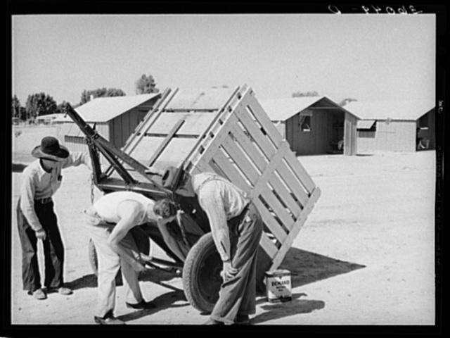 Migratory laborers inspect a trailer. Agua Fria migratory labor camp, Arizona