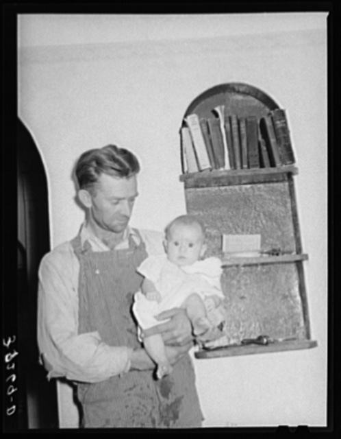 Mormon farmer with his baby in front of a bookshelf in his home. Snowville, Utah