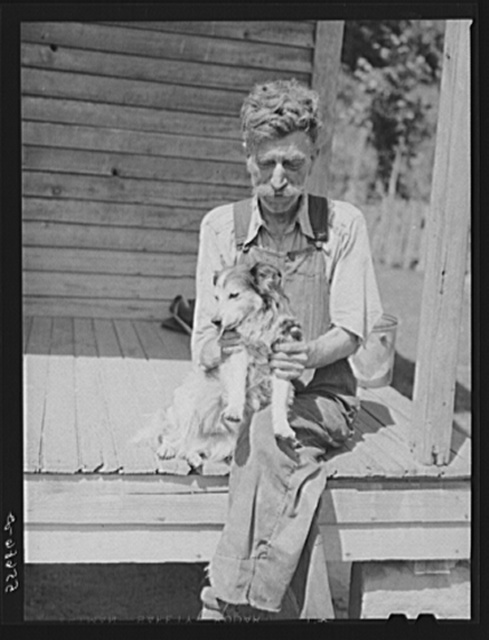 Mountaineer who reared his grandson in his home with the help of the neighbors. He had been crippled with arthritis most of his life. On the steps of a schoolhouse with his dog on South Fork of Kentucky River. Breathitt County, Kentucky