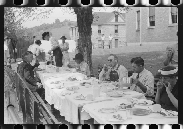 Mountaineers and farmers eating dinner served for benefit of the church in courthouse yard on court day. Campton, Wolfe County, Kentucky
