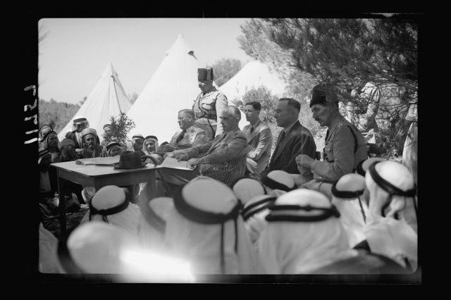 """Mr. E. Keith Roach & Mrs. K.R. entertain Sir Harold & Lady MacMichael & 500 falahen at Neby Saleh. H.E. the High Com. Mr. Sommerville, Mr. Keith Roach, etc. seated before the crowd of peasants, close up, listening to speeches made by various village """"mukhtars"""""""