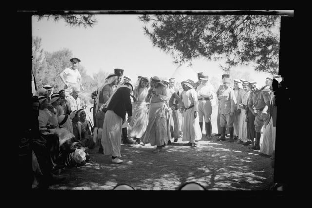 Mr. E. Keith Roach & Mrs. K.R. entertain Sir Harold & Lady MacMichael & 500 falahen at Neby Saleh. Native dance of young men after the meal, dance to rythmic flutes playing, closer up