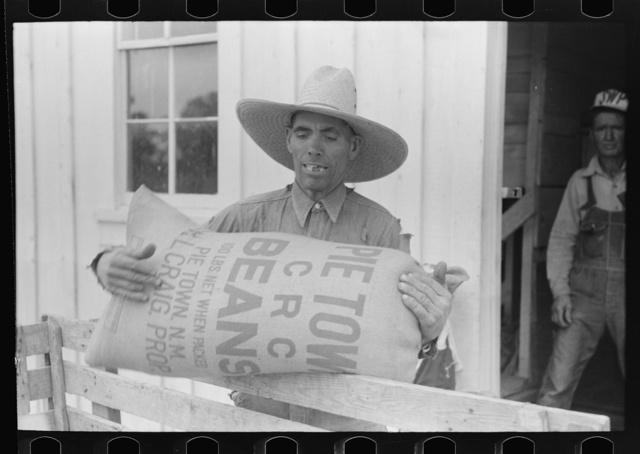 Mr. Leatherman loads a sack of pinto beans into his cart. It is cutomary for the farmers to leave their beans at the warehouse during the winter months, since Mr. Craig charges no storage fee, and get those necessary for spring planting. Pie Town, New Mexico