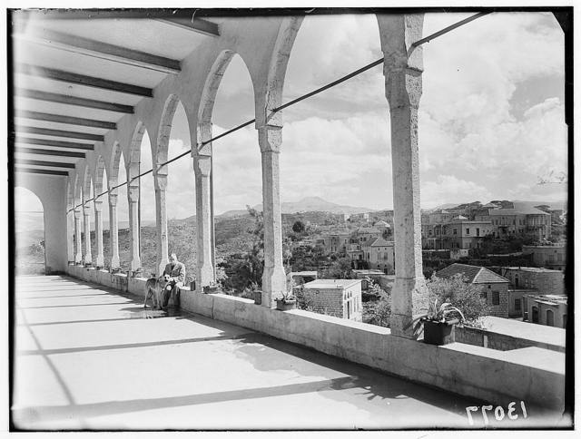 Mr. Oliver's school, Ras-el-Matn. Upper colonnade, showing village in distance. Mr. Oliver and his dog