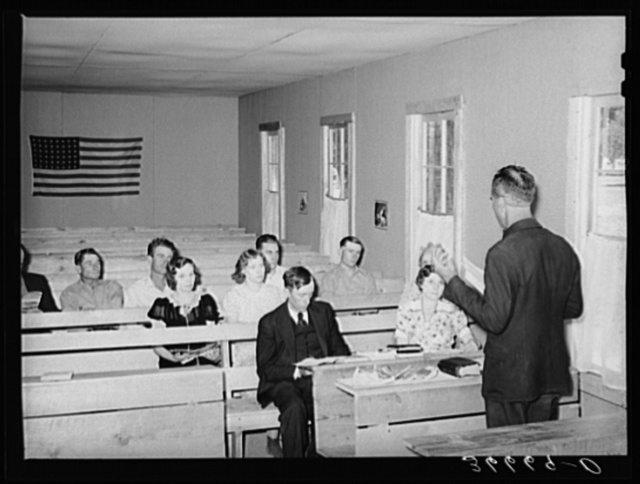 Mr. Whinery, homesteader and licensed preacher, reading the Sunday School lesson in the Farm Bureau building. Pie Town, New Mexico. Mr. Whinery donates his services as a preacher to the church