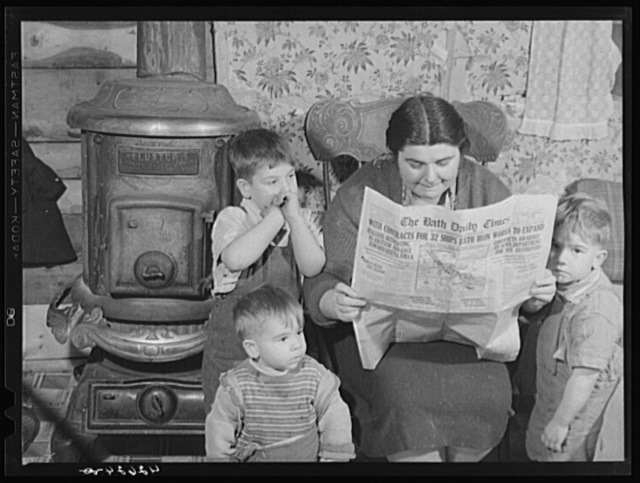 """Mrs. Arthur Brown with three of her children reading Bath Daily Times. The husband works at the shipyard. After having been away from Bath for five years returned for the """"Boom."""" Rents were too high in town and so they started building a place for themselves about five miles out of Bath on land belonging to their brother. Husband has been working a week on and a week off. One of the children is old enough to go to school but it is too far out of the way for the school bus to stop for him"""