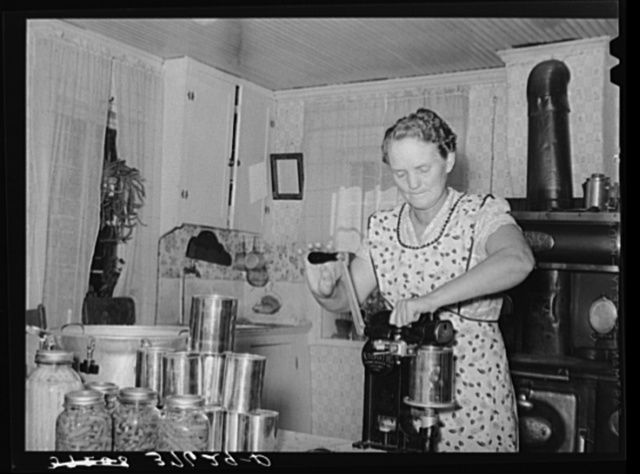 Mrs. Christiansen of the Christiansen canning unit sealing cans. During 1939 she canned 2300 quarts which included 20 mutton, 2 beeves, 5 pigs. Fish was tried very successfully. In this cooperative agreement, there were twenty-five users and outside of the cooperative there were ten others who used Mrs. Christiansen's services