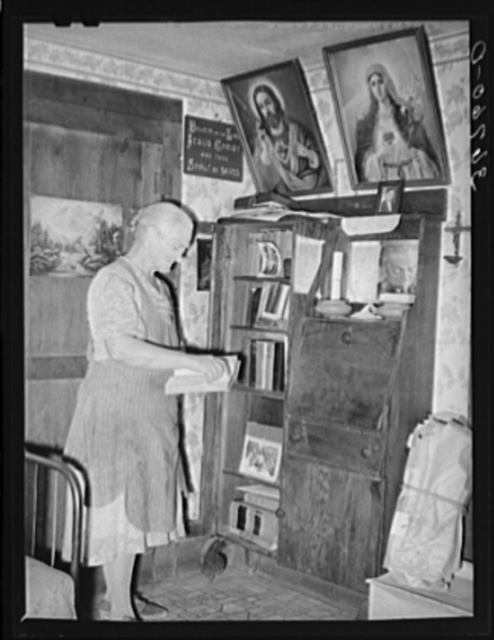 Mrs. George Hutton, homesteader, in front of her bookcase. Pie Town, New Mexico