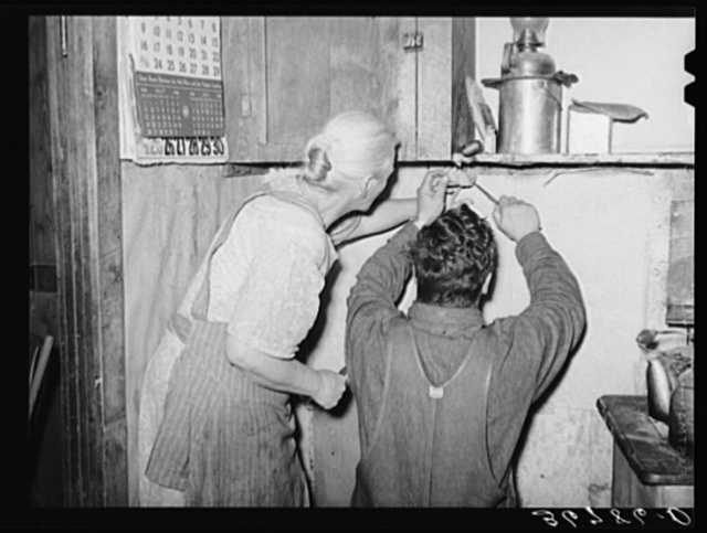 Mrs. Hutton and her son papering the kitchen. Pie Town, New Mexico