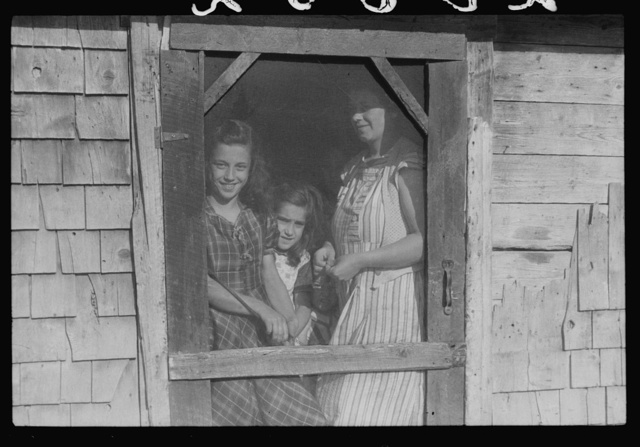Mrs. Patrick Dumond and two of her children at back door of their home in Lille, Maine. French-Canadian potato farmer and FSA (Farm Security Administration) clients