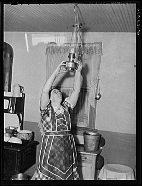 Mrs. Sauer hanging up oil lamp. Cavalier County, North Dakota