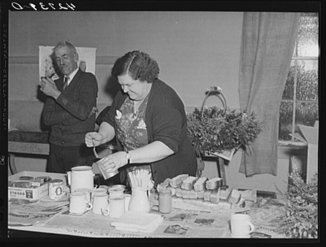 Mrs. Tucker, wife of the town police chief, preparing hot dogs and coffee at a Saturday night square dance in Clayville, Rhode Island