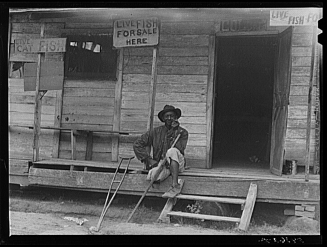 Natchitoches, Louisiana. A Negro sitting on the porch of a store where live fish are for sale