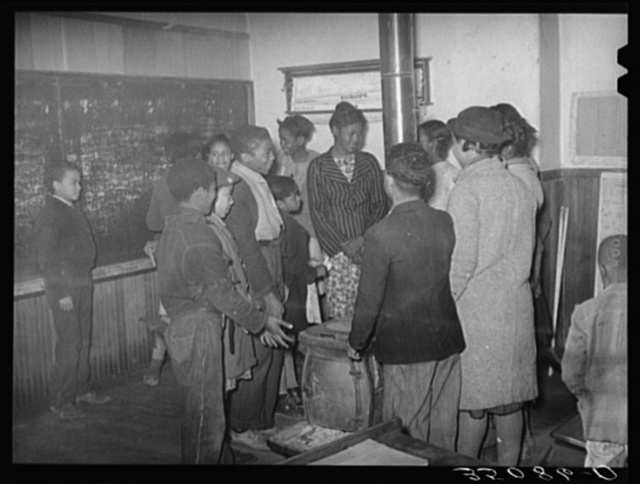 Negro children in rural school gathered around the stove as the room warms up in the morning. After school was in session the thermometer registered fifty degrees the entire morning. Creek County, Oklahoma