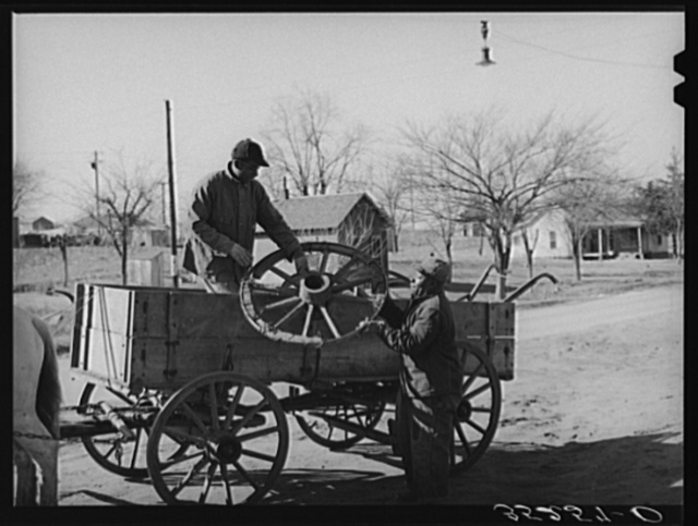Negro farmer onloading much-repaired wagon wheel at the blacksmith shop where he hopes it can again be made serviceable. Depew, Oklahoma