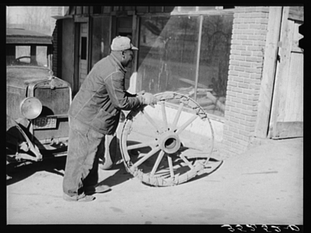 Negro farmer rolling much-repaired wagon wheel into blacksmith shop to see if it can again be repaired. Depew, Oklahoma
