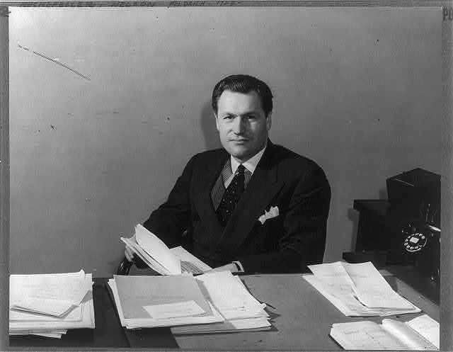 [Nelson Aldrich Rockefeller, 1908-, half length, seated behind desk, facing slightly left, papers in his hands; as Coordinator of Commercial and Cultural Relations between the American Republics]