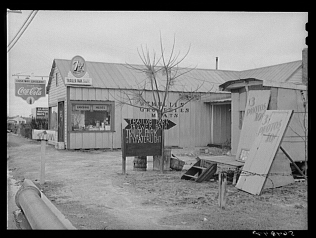 New sign in front of trailer park, and Itinerant photographer's trailer on highway near Fort Benning, Columbus, Georgia. Mr. W.T. Mullis owns property and grocery store and rents trailer space for two dollars a week to construction workers and Army men
