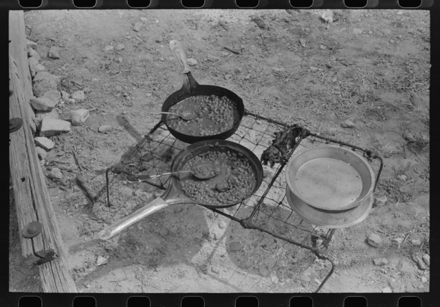 Noonday meal of professional goat and sheep shearers cooking over the campfire; pinto beans are a main item in thier diet. Ranch of rehabilitation borrower in Kimble County, Texas