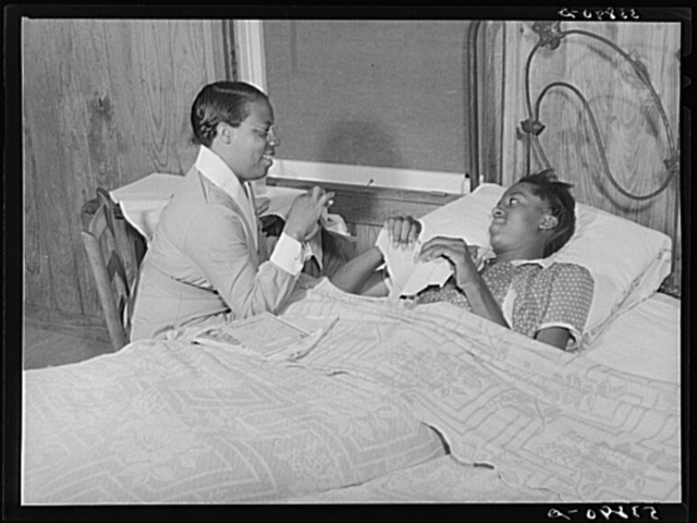 Nurse Marguerite White showing Alice Jane Holden, tuberculosis patient, how to make her own paper cups which can be burned after use in her home on La Delta Project. Thomastown, Louisiana