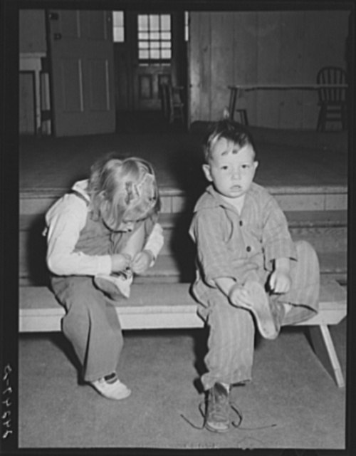Nursery children putting on shoes after nap. Shafter migrant camp. Shafter, California