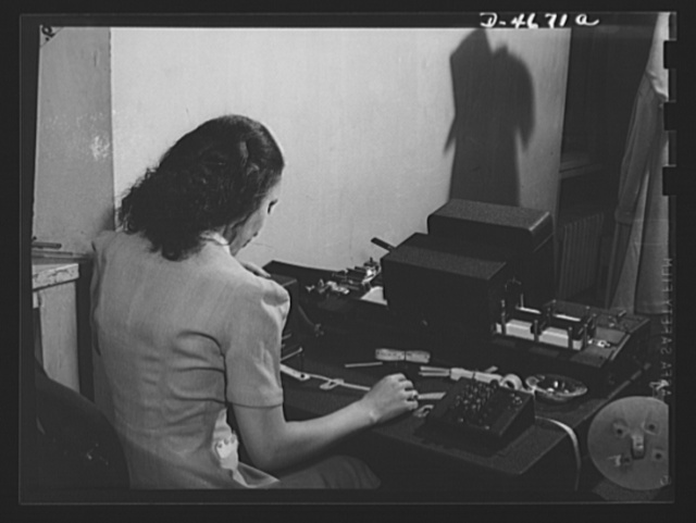 ODT system of port control. Mrs. Elsie Maddox, automatic key punch and tabulator operator in the ODT (Office of Defense Transportation), feeds the punched tape through the machine that marks the cards on traffic movement