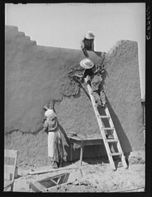 Once a year the women in the Spanish-American families replaster the adobe houses. Neighboring women are hired to help with the work. Chamisal, New Mexico