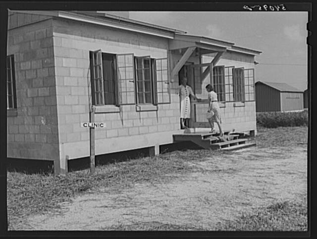 One of the camp members entering health clinic, with nurse Anne Smock in doorway. Osceola migratory labor camp. Belle Glade, Florida
