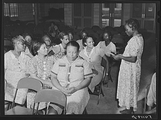 One of the camp members, vice-president of women's club, reading suggestions to group for future planning and discussions. Home management supervisor Corinne Williams sitting opposite her, encourages the members to conduct and participate in their own meeting. Assembly building at Okeechobee migratory labor camp. Belle Glade, Florida