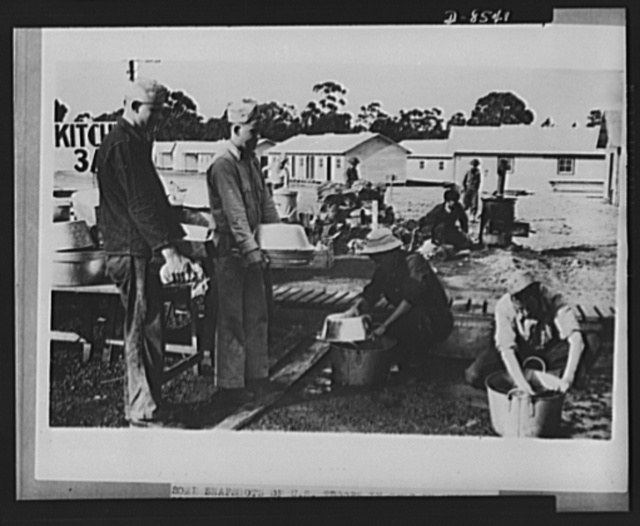 One year of reciprocal aid. American soldiers at work in a kitchen fatigue pantry in Australia, with newly-erected barracks in the background. As reciprocal aid, modern facilities like these have been built for our men without cost to the United States, not only in Australia, but in the United Kingdom, New Zealand, and the areas controlled by the fighting French as well