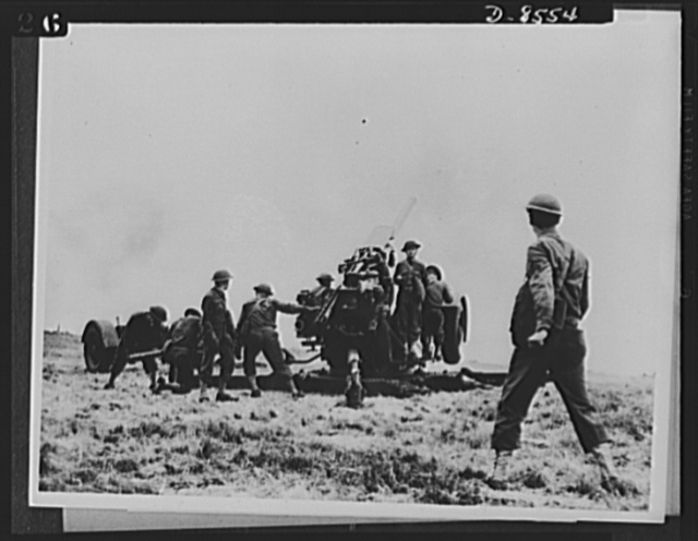 One year of reciprocal aid. Practically everything needed by our forces in Britain is supplied by the British government under reciprocal lend-lease. American soldiers here use British made guns and ammunition in training to defend U.S. bomber- fighter and aircraft repair bases in Great Britain. They are shown here firing British 3.7 inch anti-aircraft guns in Britain