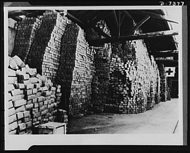 Packages for prisoners of war and internees. Americans taken prisoners of war or interned by Germany and Italy regularly receive standard American Red Cross food packages, shown here stacked like bricks in the International Red Cross warehouse at Geneva, Switzerland. U.S. prisoners of war receive one package a week as soon as the Red Cross is notified of their capture and location. Internees receive one package every two weeks. As of December 9, 1942, Germany and Italy had reported 243 American prisoners of war and 1512 interned civilians. Each package weighs eleven pounds and contains evaporated milk, buscuits, cheese, cocoa, sardines, pork, beef, chocolate bars, sugar, coffee, powered orange concentrate, prunes, cigarettes and smoking tobacco