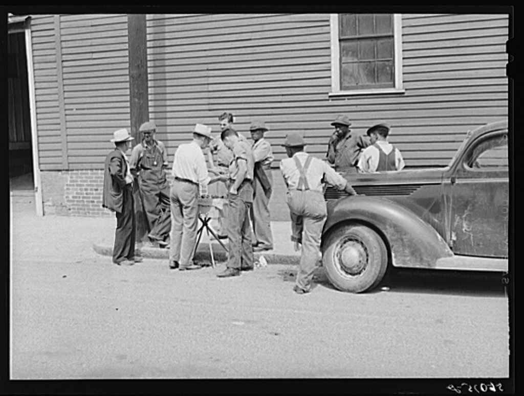 Peddler selling patent medicines to farmers outside warehouse on opening day of tobacco market in Mebane, North Carolina, where many Caswell County farmers sell their tobacco at auction
