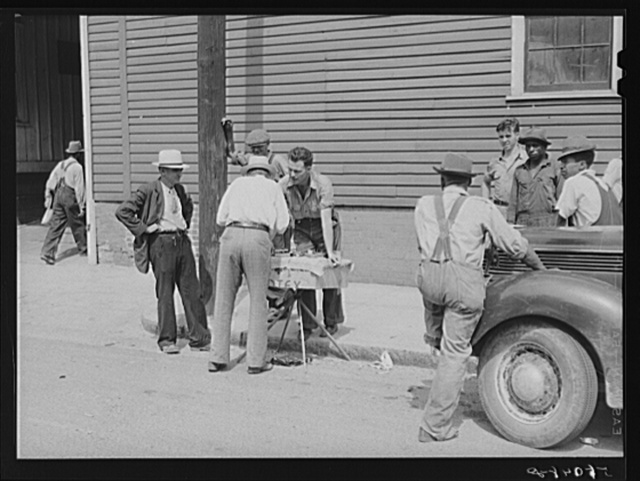 Peddler selling patent medicines to farmers outside warehouse on opening day of tobacco market in Mebane, North Carolina where many Caswell County farmers sell their tobacco at auction
