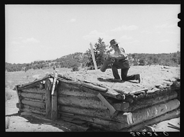 Pie Town, New Mexico. A community settled by about 200 migrant Texas and Oklahoma farmers who filed homestead claims. Faro Caudill taking down the chimney from his dugout before he tears down the dugout
