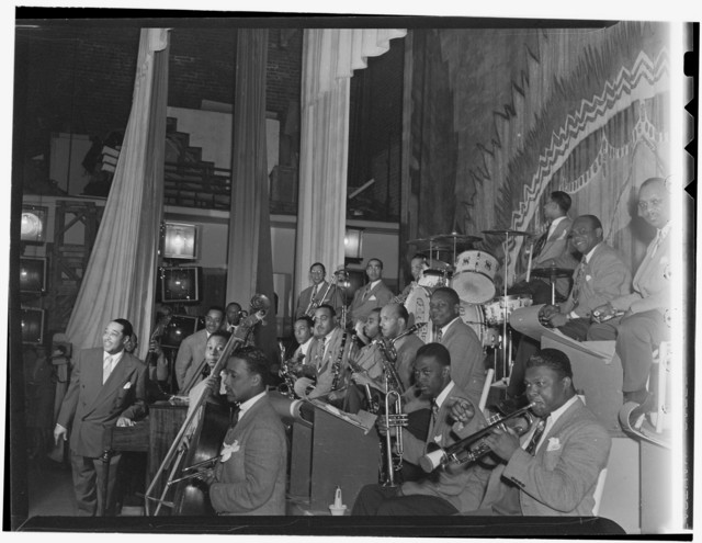 [Portrait of Duke Ellington, Ray Nance, Tricky Sam Nanton(?), Johnny Hodges(?), Ben Webster(?), Otto Toby Hardwick(e), Harry Carney, Rex William Stewart, Juan Tizol, Lawrence Brown, Fred Guy(?), and Sonny Greer, Howard Theater, Washington, D.C., early 1940]