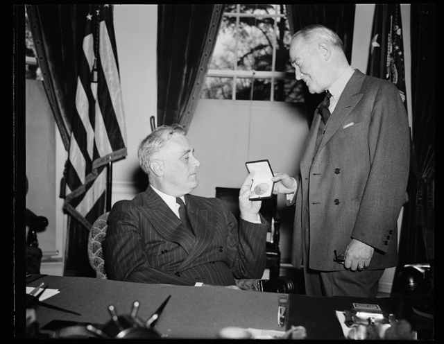 PRESIDENT PRESENTS MEDAL TO COHAN FOR 'OVER THERE' WAR SONG. PRESIDENT ROOSEVELT TODAY PRESENTED A GOLD MEDAL TO GEORGE M. COHAN IN BELATED RECOGNITION OF COHAN'S SERVICES AS COMPOSER OF TWO PATRIOTIC SONGS DURING THE WORLD WAR, 'OVER THERE' AND 'THE GRAND OLD FLAG.' COHAN WROTE THE SONG, AND MONEY FROM SALES WERE GIVEN TO CHARITY. THE MEDAL WAS AUTHORIZED BY CONGRESS IN 1936. IN THIS PHOTOGRAPH IS SOME RESEMBLANCE IN COHAN TO PRESIDENT ROOSEVELT WHOM HE CHARACTERIZED IN A RECENT PLAY