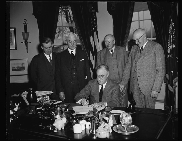 PRESIDENT SIGNS BILL EXTENDING RECIPROCAL TRADE PROGRAM. WASHINGTON, D.C. APRIL 12. PRESIDENT ROOSEVELT PICTURED SIGNING TODAY THE BILL EXTENDING FOR THREE YEARS THE POWER OF THE UNITED STATES TO NEGOTIATE RECIPROCAL TRADE TREATIES WITH FOREIGN POWERS. DIRECTLY BACK OF THE PRESIDENT, L TO R: SECRETARY OF STATE CORDELL HULL; SECRETARY OF AGRICULTURE HENRY A. WALLACE; SENATOR PAT HARRISON, CHAIRMAN OF THE SENATE FINANCE COMMITTEE; REP. ROBERT DOUGHTON, CHAIRMAN OF THE HOUSE WAYS AND MEANS COMMITTEE. THE PASSING OF THIS BILL WAS ONE OF THE MAJOR NEW DEAL VICTORIES OF THIS SESSION OF CONGRESS