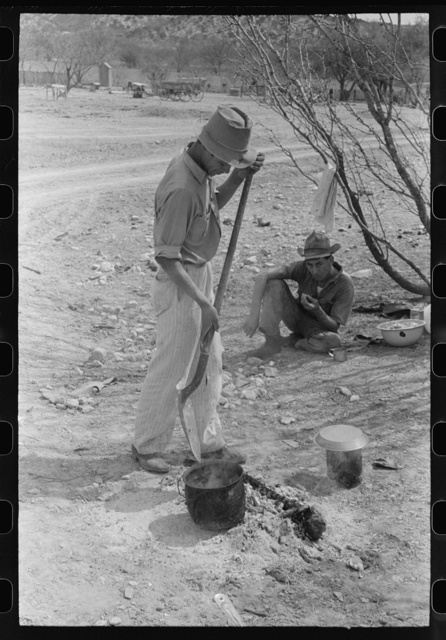 Professional goat and sheep shearer moving kettle closer to the coals while he cooks the noonday mean on the ranch of a rehabilitation borrower in Kimble County, Texas