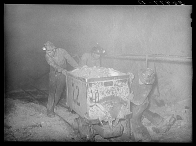 Pushing a car load of gold ore along track in mine. Mogollon, New Mexico