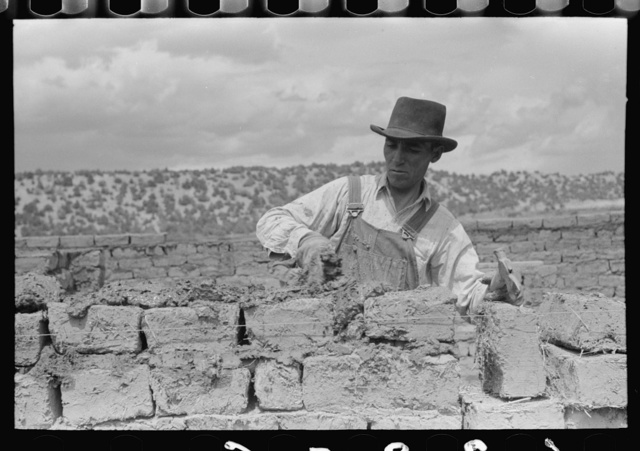 Putting adobe plaster between adobe bricks in construction of house, Penasco, New Mexico