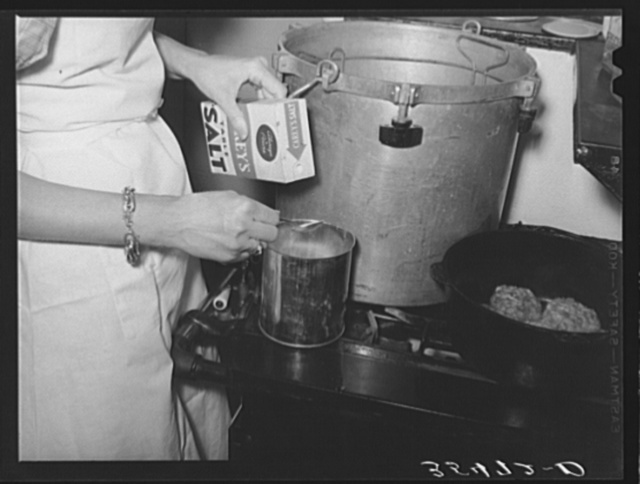Putting salt in a can in which meat will be canned using the pressure cooker method. This was during the demonstration by a FSA (Farm Security Administration) supervisor at a district meeting of FSA officials. San Angelo, Texas
