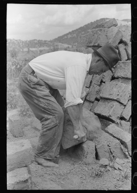 Removing the rough edges from adobe bricks with a trowel, Penasco, New Mexico