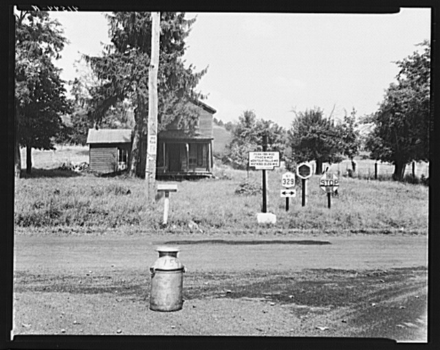 Road intersection with milk can waiting to be picked up by delivery truck. Townsend, New York