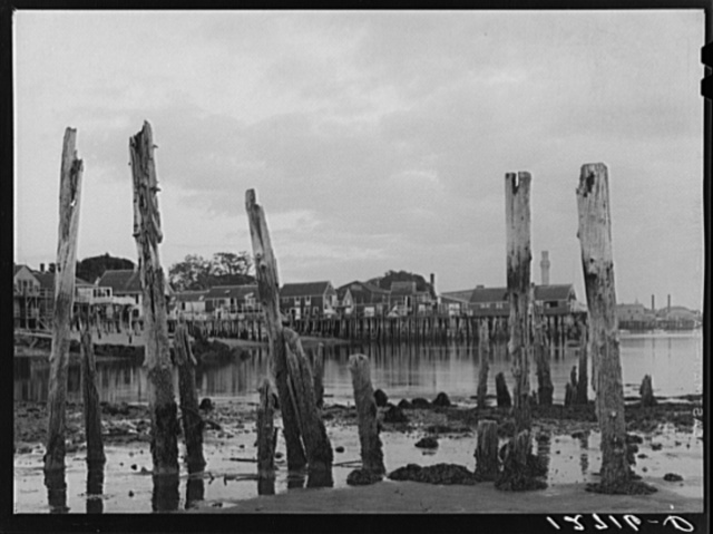 Ruins of former fish pier, Captain Jack's Wharf, a tourist colony which used to be a fish pier and the Pilgrim monument in the background. Provincetown, Massachusetts