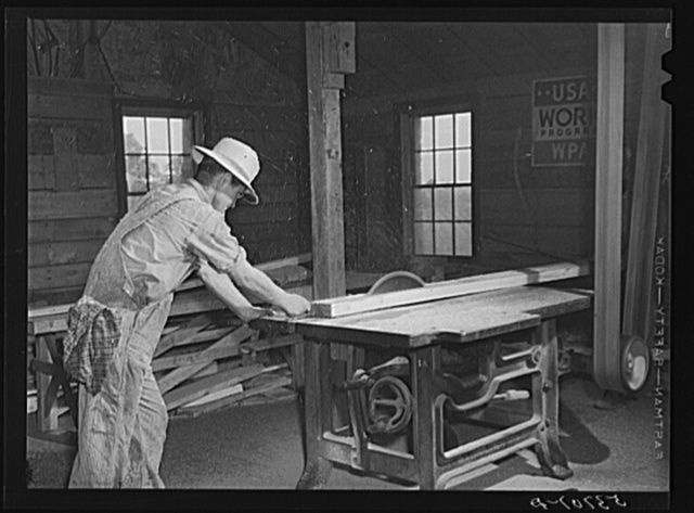 Sawing board in woodworking shop. Community service center, Centerville, Arkansas. Faulkner County (see general caption)